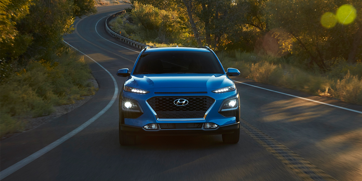 Washington Hyundai is a Hyundai Dealership in Washington near Canonsburg PA | Blue 2020 Kona Driving Down Country Road at Sunset